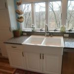small kitchen set with double farm sinks in white beautiful and luxurious marble countertop hanging decorative fruits a fried-clay  pot with green vivid plant ornament kitchen glass windows without drapes