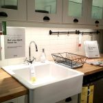 square white farm sink and faucet for kitchen a metal-wire basket for storing clean dishware  wood countertop