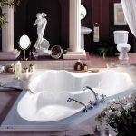 wonderful built-in tub for couple with double faucet fixtures in luxurious bathroom a toilet fixture red ceramic tiles floors a standing sink fixture with faucet round decorative mirror an artistic statue