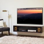 wood floating media console with shelves DVD player sound system flat TV a single black chair with white pillow small side-table with some decorative stuffs stand-lamp white fury
