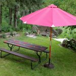wood  picnic table in modular shape with black-staining  a big red outdoor shed looks like big umbrella  two backless blackwood modular chairs