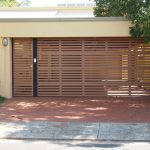 Batten cool garage doors for single car in brown scheme with brick paver floor and plant