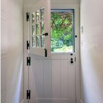 Dutch door in barn door style with glass panel with trims in top section