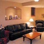 Living room basement finishing with black leather seating and arch wall niche plus mini lamp shade