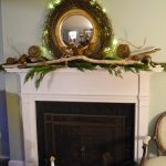 A Fireplace With Closed Door Panel And Tiny Driftwood Mantle On Top A Round Decorative Mirror With Wreath Ornament