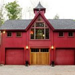a unique red private pole barn house with roof castle-look like and metal siding and  wood front door two red metal garage doors