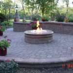 adorable-cool-classic-nice-simple-patio-with-fire-pit-with-ignited-pit-and-has-some-flower-decoration-with-nice-brick-wall-and-floor