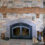 adorable rustic driftwood mantle idea upon gray fireplace with two doors and stone mantle before wooden stool with lantern on wooden floor