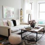 adorable white modern living space design with white seating and metal rectangle coffee table upon black patterned area rug with round puff aside ladder storage design