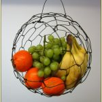 adorable wire wall mounted fruit basket design with green grape and oranges and banana before white wall