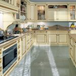 amazing antique kitchen cabinet design with smooth cream color and flashing brown line accent with wooden countertop and a vas of flower and white backsplash and grey floor