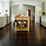 amazing black bamboo flooring style in kitchen beneath natural wooden kitchen cart with stainless tools aside white cabinetry idea and glass windows with red flower on the countertop