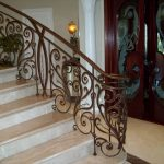 amazing classic wooden door design with stunning dragon pattern aside staircase with wrought rod iron railing design