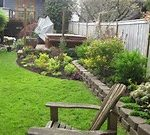 amazing green landscape design seattle with grassy meadow and natural stone parting and beautiful garden with wooden chair