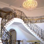 amazing modern chandelier design with double staircase in white concrete design with wrought black rod iron railing