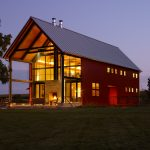 amazing pole barn house design with tall double height interior and golden lighting with reddish wall design surrounded with grassy meadow aside a tree with american roof style