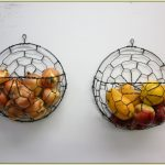 amazing round wire wall mounted fruit basket design with round flat net wire base stacked on the white wall and lemonade and appple and garlic