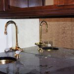 antique mirror backsplash a deep round gold sink  and gold faucet
