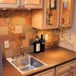 appealing brown tile backsplash mixed with luminous glass door cupboard and grey fridge plus catchy base cabinet in small basement wet bar