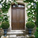 awesome wooden classic front door idea with carved design and metal trellis between two side creamwall before stunning green white plant decoration and double shrub