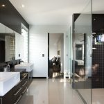 awsome modern bathroom design with small tile walk in shower with transparent door and floating luxurious vanity with flashing white wall acent and double sinks