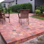 basket weave brick paver patterns for raised patio with stack bone edge combined with traditional armchairs in garden with plants and grass in backyard