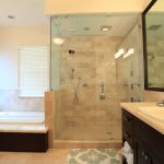 bathroom remodelling with bathtub and walk in shower with glass and vanity units plus sink and large size windows and pretty wall scones