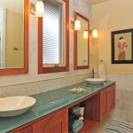 bathroom remodelling with modern bathroom vanity units plus glass countertop and double sinks combined with mirrors and wall scones plus tile floor and wall