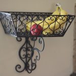 beautiful black wall mounted fruit basket design with scrolled metal material in rectangle style with tail with banana and apple inside