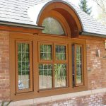 beautiful cottage style windows with light brown wood material in casement design plus clear glazing on cool brick wall