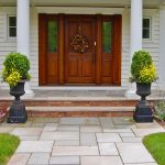 beautiful double front door design with glass and wood panel beautified with wreath and cool wall with pretty plant pot and patio and natural floor