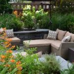 beautiful landscape design seattle with wonderful natural stone fence behind comfortable cream sofa bed for seating and flashing orange flower