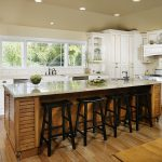 Beige Bambooo Floring In Kitchen With Wooden Island Design Before Black Wooden Stools Beneath Small Recessed Ceiling Lamps Aside White Cabinetry With Some Greenery