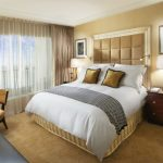 beige bedroom ideas with divan bed and large headboard and wooden nightstands with table lamps and pictures on wall and rug are and cute chair and pretty vase