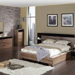 beige bedroom ideas with wooden frame panel bed plus nightstand and sideboard plus table lamp and soft rug on wooden floor and mirror and brick wall