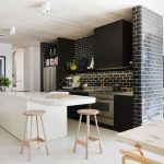 black and white brick wall for kitchen plus black wooden cabinets and white kitchen island with sink and wooden stools plus large picture and kitchen appliances