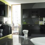 black bathroom design with large back vanity with flashing green line accent and stunning upper storage and glossy black floor and toilet seat modern sink and bathtub