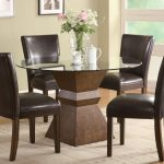 casual black cowhide dining chair design with round glass dining table with wooden geometrical beam with flower and pictures on the grey wall with large glass window
