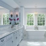 classic bathroom with small tub with faucet modular bathroom vanity with Carrara marble surface and double sinks plus faucets large-wall mirror  no frame classic pendant light Carrara marble floor