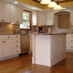classic glass pendant lamps overlooking with plain color wooden cabinet and kitchen island in brown laminate floor and yellow wall color by nice kitchen remodel contractors