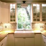 classic tiny kitchen remodel with white wooden cabinets and countertops plus sink and glass back splashes and topper with dining set