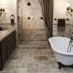 claw foot tub on rustic beige tile floor and backsplash for fetching bathroom in best remodel with classic sconces and wooden furniture plus silk curtain door