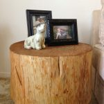 clear stained wood stump side table with casters two picture frames in black an animal miniature