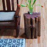 cool and darker stained tree trunk side table beautiful glass as a pot for decorative plant a wood chair with brown leather seating flower patterns rug for wood planks floors