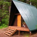 cool and unique cabin construction in woods with rustic front door and wood stairs and also lightweight metal roofing