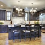 cool kitchen remodeling with dark wood cabinets and marble countertop plus island with sink and microwave refrigerator together with brick wall and refrigerator