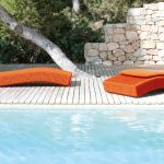 cool outdoor lawn chair with back and headrest features but no armrest feature  a large swimming pool