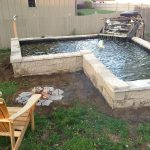 cool simple in ground fire pit design aside pond with concrete edge before wooden lawn chair above grassy meadow