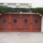 cool wooden garage doors in brown plus plant and white scheme wall combined with brick paver floor