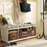 corner main entrance bench with strorage two pairs of shoes a round chair with a basket of fruits cloth hanger stand made from black metal white entryway rug hard wood floor